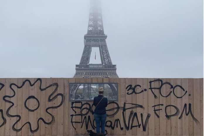 A woman looks at the Eiffel Tower through a hole in a fence.