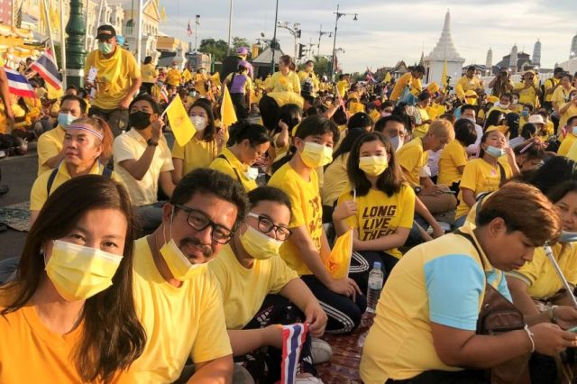 A crowd of people wearing masks and holding yellow flags while wearing yellow shirts sit on the ground in a street.