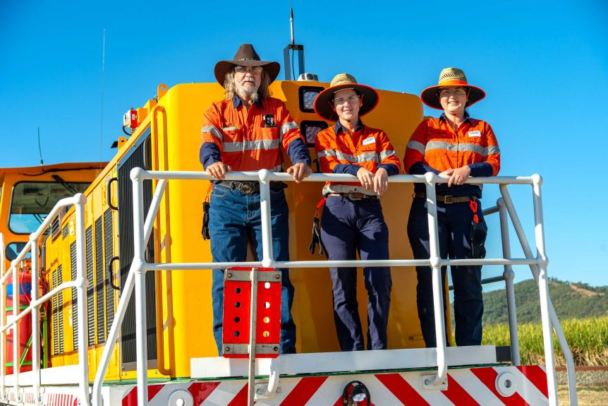 three people stand at the front of a cane train