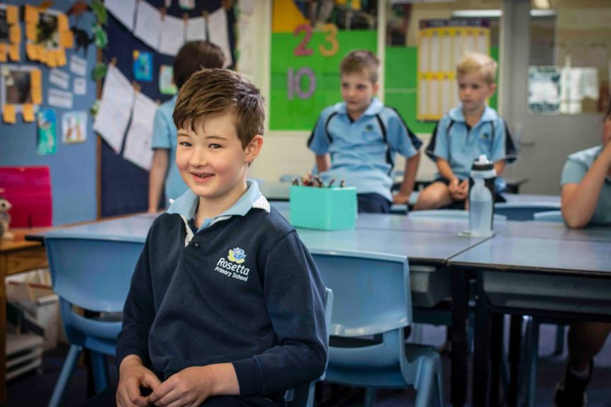 A primary school boy smiles at the camera
