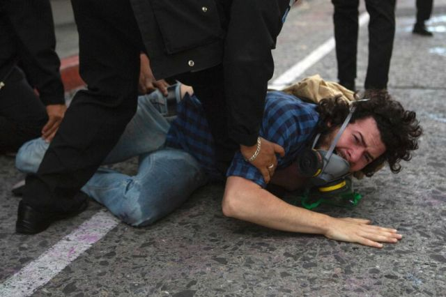 A man is held on the ground while being detained by police near the Guatemalan Congress building