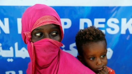 A woman wears a pink headscarf as she stands with her young child at a refugee camp