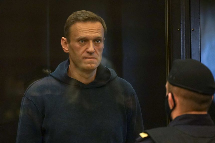 A man in a navy hoodie stares in the distance in a courtroom.