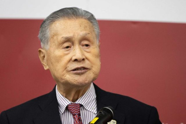 Yoshiro Mori, wearing a black suit, speaks into a microphone