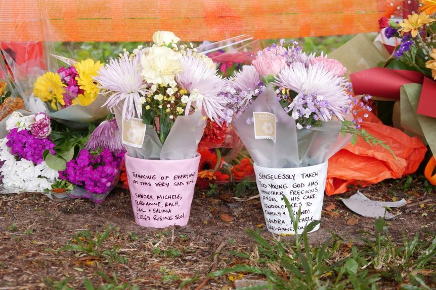 A close-up of two flower bunches with notes written to the victim.