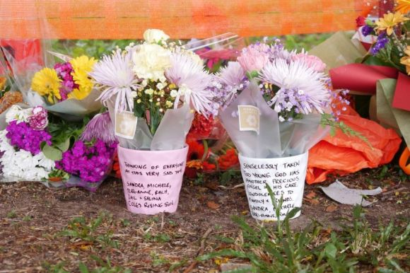 A close up of two flower bunches with notes written to the victim.