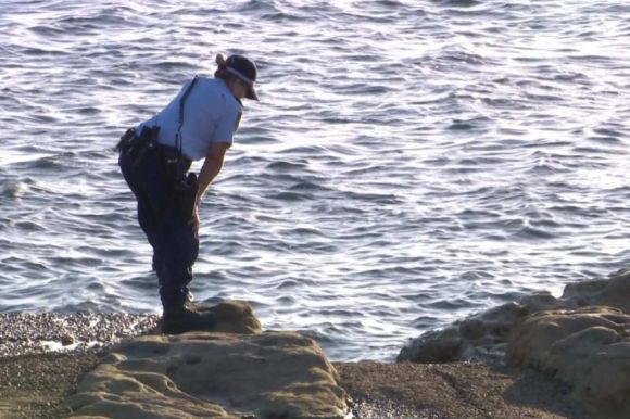 A female police officer stands on a rock, leaning over to look into water