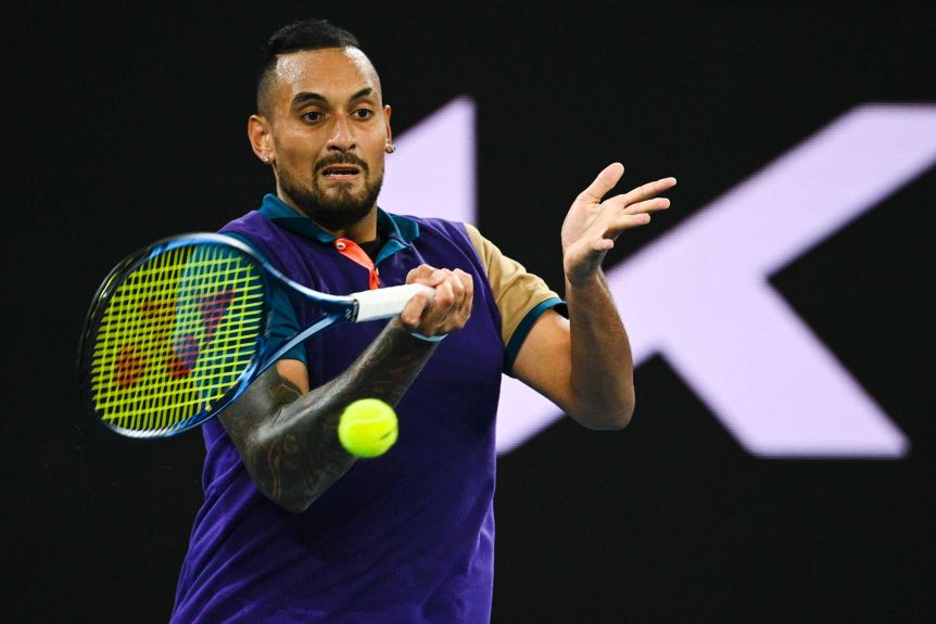 Nick Kyrgios grimaces as he makes contact with a forehand