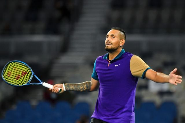 Nick Kyrgios holds his arms out and smiles while looking up towards the crowd