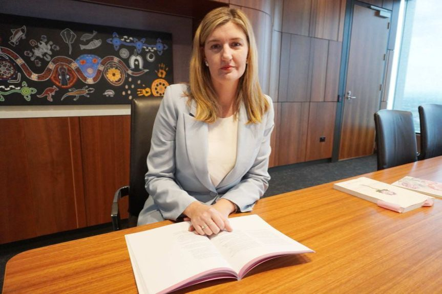 A woman sits in a board room.