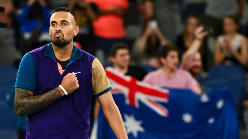 Nick Kyrgios pumps his fist against his chest with an Australia flag in the background