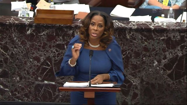 Stacey Plaskett, dressed in blue, speaks at a lectern in the US Senate