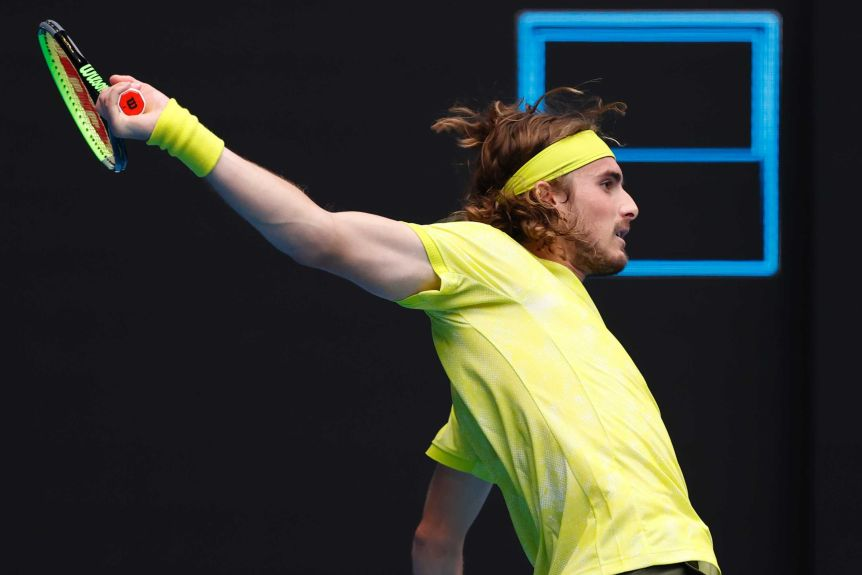 Stefanos Tsitsipas completes a backhand with the racquet well behind him at the Australian Open.