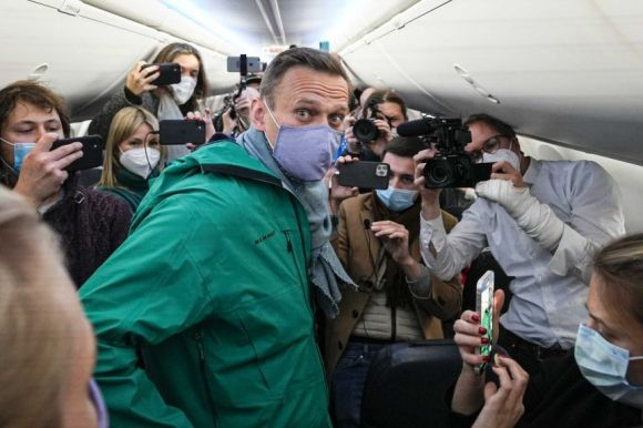 Alexei Navalny surrounded by reporters on a plane.