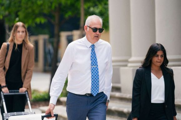 Francis Wark's lawyer Darryl Ryan walking outside court wearing sunglasses and a blue tie, with women to his left and right.