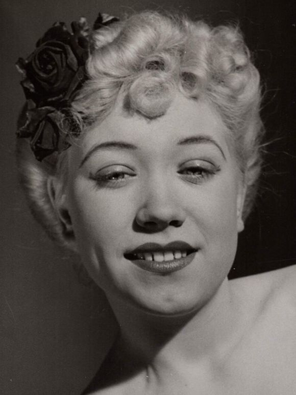 A platinum blonde young woman in a black and white glamour shot.