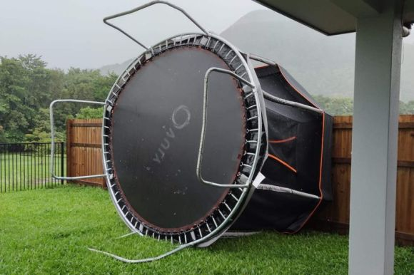A trampoline is on its side against a fence.