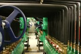 A series of green pipes in a basement room.