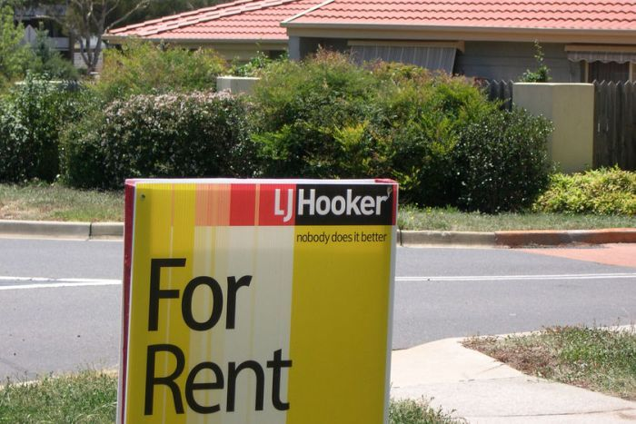A sign saying for rent stands outside a suburban home.