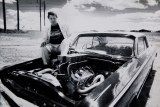 The founder of Summernats, Chic Henry, sits on the bonnet of a modified car.