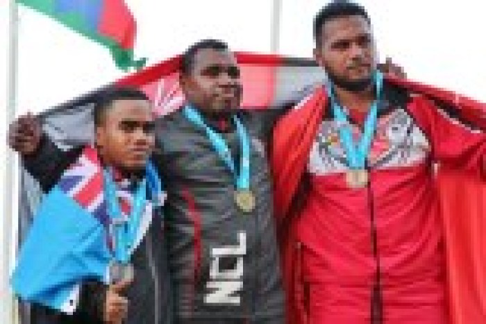 Iosefo wrapped in the Fijian flag and posing for photos with other medallists, also wrapped in flags.