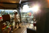 Production crew setting up lights and cameras on balcony overlooking sporting precinct with sun in shot.