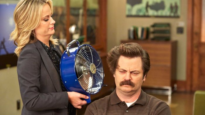 Amy Poehler, playing Leslie in Parks and Recreation, holds a blue fan up to the face of Ron, played by Nick Offerman