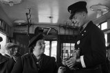A London bus conductor collects a fare from a woman. Black and white photo.