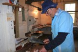 Paul 'Spud' Bennett cutting to the final off-cuts in his butcher shop.
