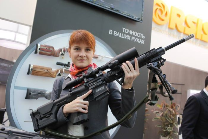 Maria Butina, a young woman with red hair, poses with a large gun, smirking at the camera.