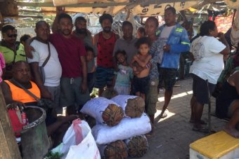 A group of people stand in front of stacks of betel nut in PNG.
