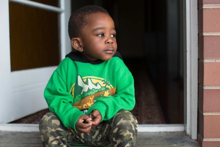 Two-year-old Mortada sits on the front porch and looks off to the side