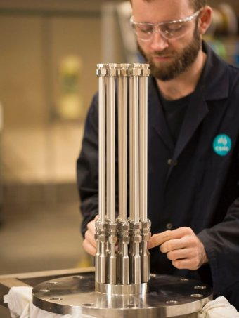 A researcher stands with H membrane technology device.