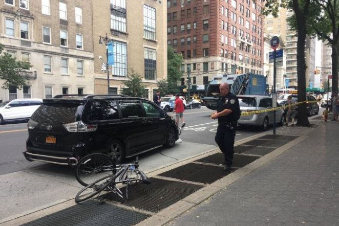 A police officer at the scene after a cyclist was hit and killed by a garbage truck.