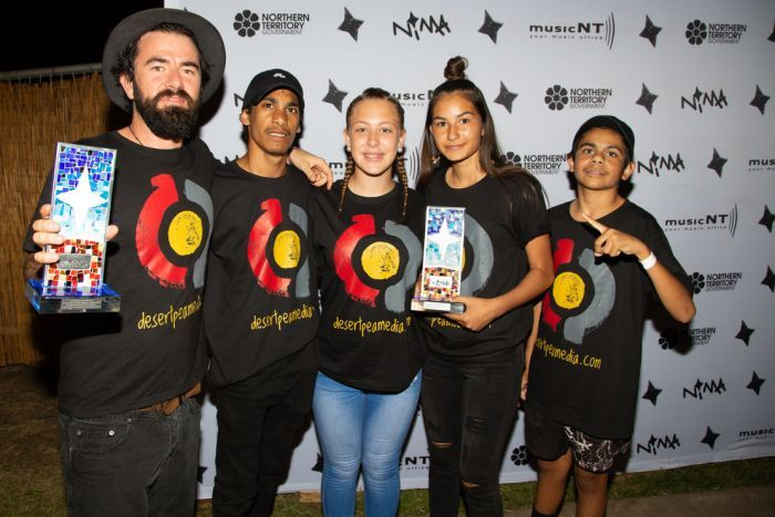 Five people stand in t-shirts with the words Desert Pea Media and a red, yellow and grey symbol on it, some holding awards.