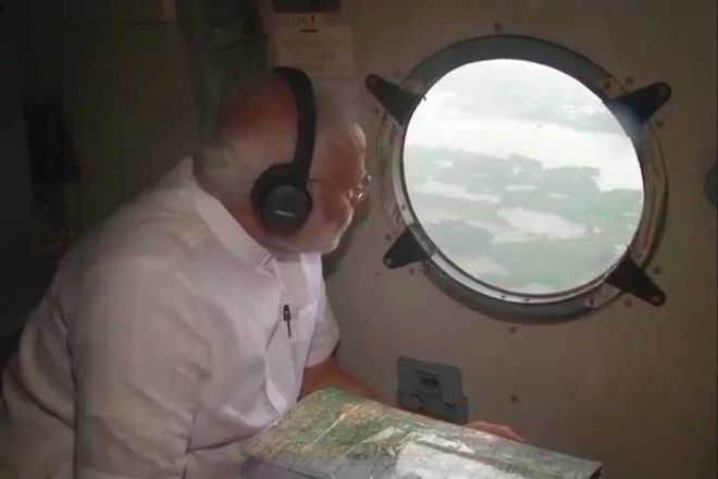 Indian Prime Minister Narendra Modi looks out from inside a helicopter to see flood