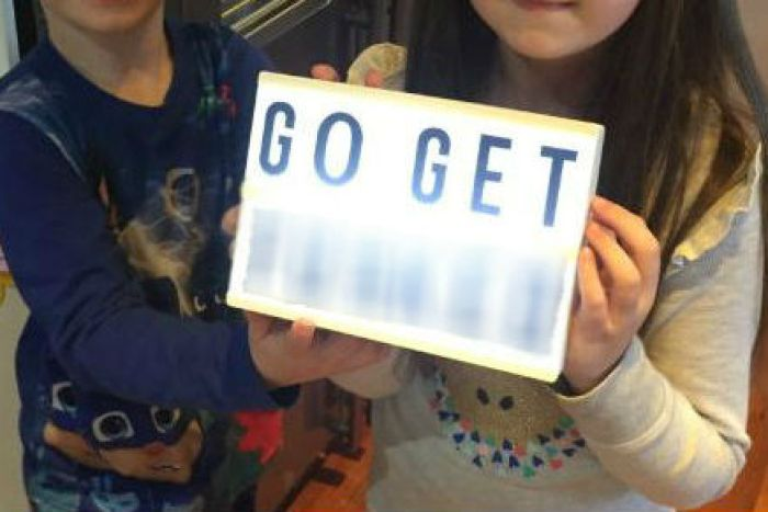 """Two children wearing pyjamas hold up a lightbox with the words """"go get f***ed"""" on it. The last word is blurred out."""