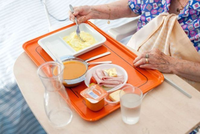 An older woman eats from a tray of bland-looking food, including ham and soup.