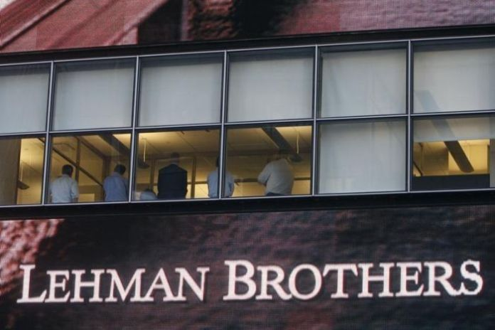 People are sitting in the window at the Lehman Brothers building in New York on September 15, 2008.