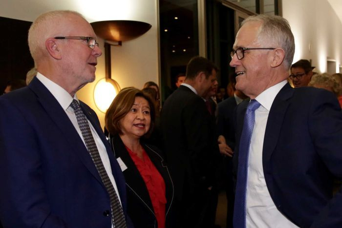 Justin Milne, Michelle Guthrie and Malcolm Turnbull stand together for a photograph at an evening function.