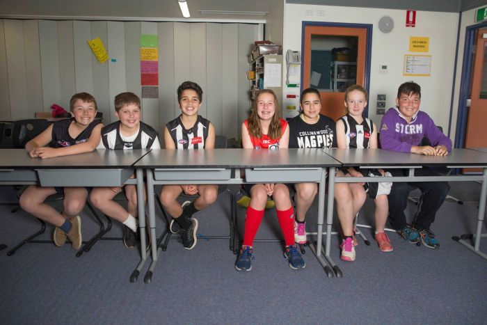 Students at Mickleham primary school sitting at their desks in their footy gear