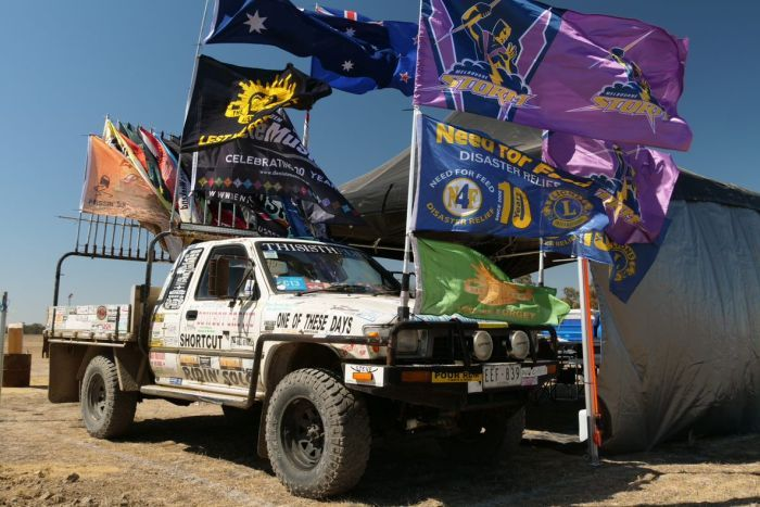 A white ute decorated with stickers and flags