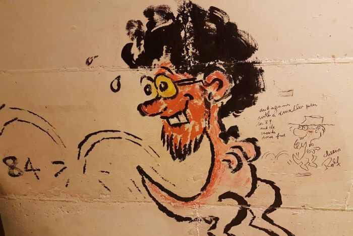 Two sketches of a man's face with black curly hair wearing glasses on a kangaroo's body on a pale coloured wall