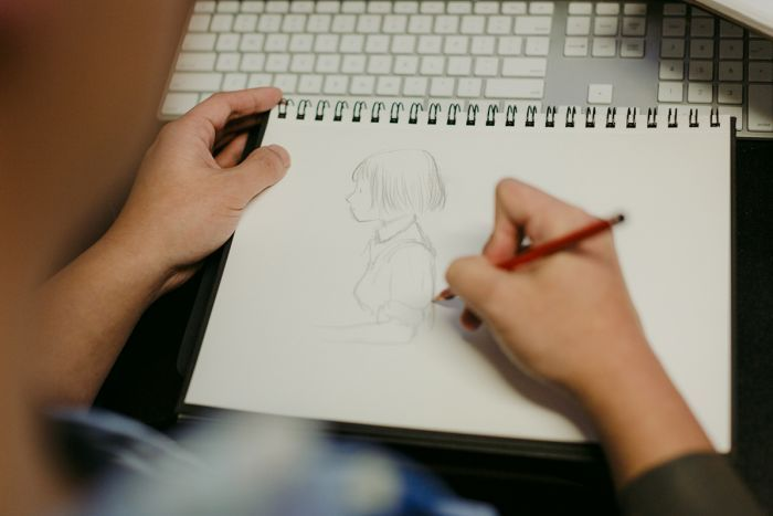 Colour photograph of games designer Ken Wong sketching Florence, the hero of his mobile game of the same name.