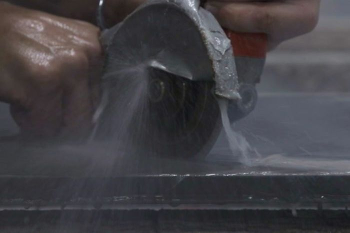A person wet-cutting stone