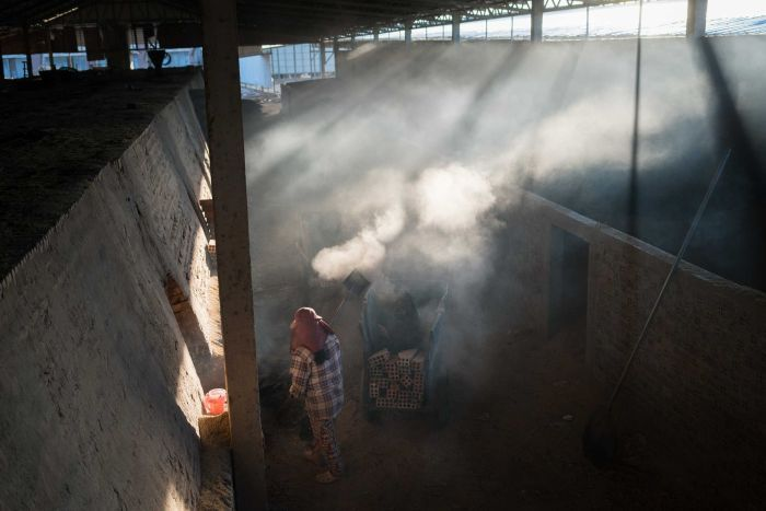 A woman cleans ash from a brick kiln in Cambodia.