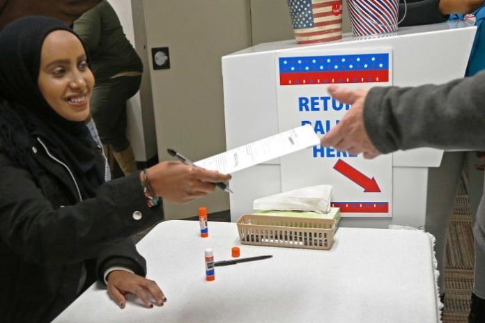 A judge awards his ballot to an early voter.
