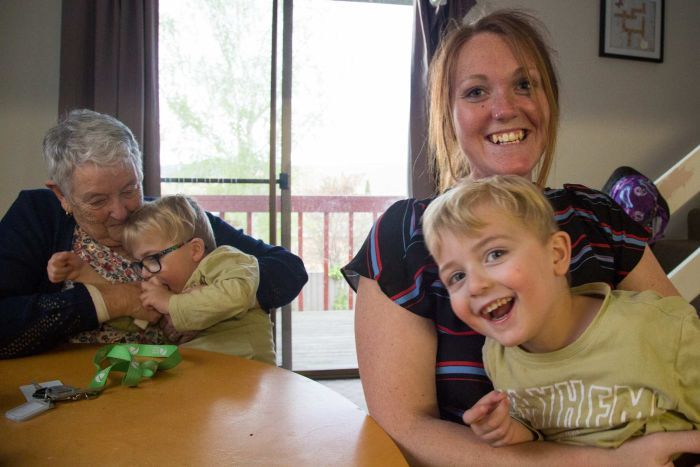 Naomi and her grandmother Carol sit at the kitchen table each  holding on to an energetic four-year old boy.