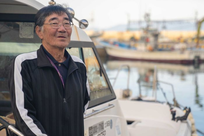 A shot of a 71-year-old man aboard his boat in a port