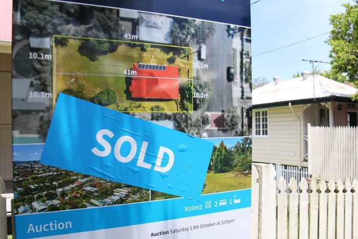 Sold sign on Queenslander-style house in a street in Brisbane.